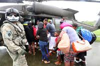 Evacuees board a waiting National Guard Black Hawk helicopter on the basketball court of Valley View Apartments in Port Arthur Texas. (Rick Moon/Special Contributor)