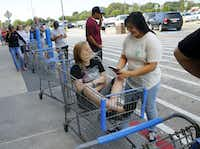 Jessica Puffen, 16, waited in a shopping cart along with her friend Emily Gomez, 17,  in a long line at  the Walmart on Hwy. 35 in Pearland, Texas.(Tom Fox/Staff Photographer)