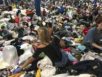 "Kathryn Loder of West University separates donated clothing from a huge pile at the George R. Brown Convention Center. ""I'm so proud how everyone is coming together,"" said Loder in her second day of volunteering. (Elizabeth Conley/Houston Chronicle via AP)"