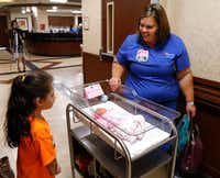 Narale Negrete, 7, watches as RN Colleen McGuire takes her newborn baby sister Ximena back to her room. (David Woo/Staff Photographer)