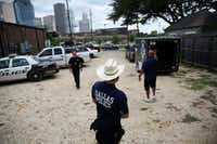 A Dallas police officer waits while a truck is backed in as members of the Dallas Police Association donate relief items collected for the Houston Police Department are dropped off at the Houston Police Officers' Union in Houston Wednesday August 30, 2017. The Dallas Police Association organized donations in assistance to police officers that are working following the devastation cause by Hurricane Harvey.(Andy Jacobsohn/Staff Photographer)