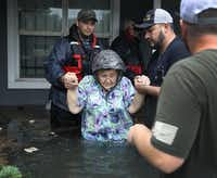Volunteer rescuer workers help a woman from her home that was inundated with the flooding of Hurricane Harvey on August 30, 2017 in Port Arthur, Texas. Harvey, which made landfall north of Corpus Christi late Friday evening, is expected to dump upwards to 40 inches of rain in Texas over the next couple of days. (Joe Raedle/Getty Images)