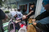 Stacie and Shane Montie and their pets board an airboat driven by volunteers Erik Davis, left, and JV Bagley, right, of Carthage, Texas as they evacuate rising waters from Hurricane Harvey on Wednesday, August 30, 2017 in Lumberton, Texas. (Ashley Landis/Staff Photographer)