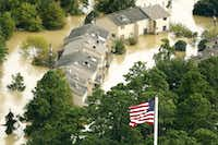 The U.S. flag flies before flooded condo buildings sitting in the the overflowing San Jacinto River in Humble, Texas, Wednesday, August 30, 2017. Hurricane Harvey inundated the Houston area with several feet of rain. (Tom Fox/Staff Photographer)