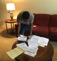 <p>Fred Rooters sorts through paperwork in his mother's living room as he tries to figure out her legal case.</p>(Sarah Mervosh/Staff)