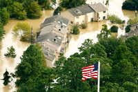 The U.S. flag flies before the River View Townhomes which are surrounded by the overflowing San Jacinto River in Kingwood, Texas, Wednesday, August 30, 2017. Hurricane Harvey inundated the Houston area with several feet of rain.(Tom Fox/The Dallas Morning News)