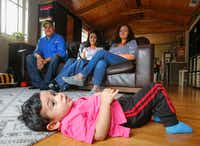 Eighteen-month-old Noah Sosa lies on the floor of a house found through Airbnb, under the watchful of eye of his grandfather, Julio Gonzalez, left, America Gonzalez, center, mom and grandmother, America Villarreal, Wednesday August 30, 2017.  The family, from New Caney, north of Houston, left their home before Hurricane Harvey hit. (Ron Baselice/The Dallas Morning News)(Ron Baselice/Staff Photographer)