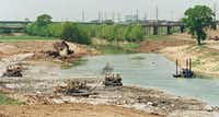 Construction workers dig out the  Trinity River channel north of the Corinth Street Viaduct in 1996 to shore  up levees in case of a major flood in Dallas. More work was done to reservoirs and floodway systems after Hurricane Katrina.(The City of Dallas)