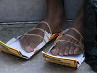 Jeremiah Ward wears his makeshift shoes after he was rescued in the 9th Ward on Aug. 30, 2005 in New Orleans after Hurricane Katrina.(Irwin Thompson/The Dallas Morning News)