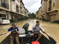 Dallas residents Josh Womack and Sammy Abdullah paddle through a row of townhomes on a search-and-rescue trip in the Kingwood neighborhood of Houston on Aug. 29.(David Tarrant/Staff)