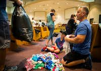 Tanner, 10, and Tab Burton and other volunteers fold donated clothes in a shelter at Woodcrest Church in Lumberton.(Ashley Landis/Staff Photographer)