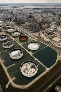Large storage tanks situated in retention ponds are surrounded by rainwater left behind by Hurricane Harvey at ExxonMobil's refinery in Baytown, Texas, Wednesday, August 30, 2017.(Tom Fox/Staff Photographer)