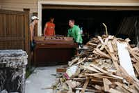 Joey Dill (left), his brother Josh Dill (center) and Josh's brother-in-law John Hallmark (right) remove a piano from Josh's house as demolishing and cleaning continue as the Dills recovery after flooding from Harvey in Kingwood, Texas Thursday August 31, 2017.(Andy Jacobsohn/Staff Photographer)