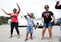 Josiah Anderson, 6, of Beaumont sings as T-Mobile employees Karmen Brown (left) and Vanessa Ibarra (right) dance to the music outside the Walnut Hill Recreation Center in Dallas.(Vernon Bryant/Staff Photographer)