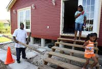 In August 2008, James Ackerson prepared to board up his newly rebuilt home in the 9th Ward in New Orleans as his daughters, Jardyn and Jaetlya, carried last-minute food supplies to the family car.(File Photo/Staff)