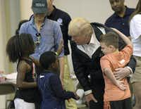 President Donald Trump and his wife, Melania, meet people affected by Hurricane Harvey on Saturday during a visit to the NRG Center in Houston. It was his second trip to Texas in a week, and this time his first order of business was to meet with those barred from their homes by the record-setting rainfall and flooding. (Susan Walsh/The Associated Press)