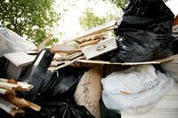 """One family scribbled """"Harvey"""" on a trash bag in the front yard. They wrote """"Harvey wuz here!""""and """"yuck"""" on a wooden piece of furniture also left outside the home.(Andy Jacobsohn/Staff Photographer)"""