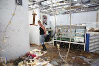 Melissa Smith, owner of the Always Sunny Fudge and Ice Cream in Rockport, walks through her shop while cleaning up storm damage on Wednesday.<div><br></div>(Rose Baca/Staff Photographer)