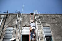 John Paul Frederick, co-owner of the Estelle Stair Gallery, climbs to the roof to help with repairs in Rockport, Texas on Thursday, Aug. 31, 2017.(Rose Baca/Staff Photographer)