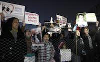 Immigration reform protesters gather outside the fence for the lighting of the 2013 U.S. Capitol Christmas Tree, an 88-foot Engelmann spruce, from the Colville National Forest, in northeast Washington State, during an event on Capitol Hill in Washington, Tuesday, Dec. 3, 2013.(Susan Walsh/AP)