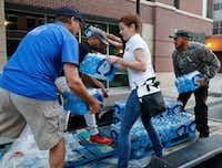 Pedro Frias, 31, of Dallas helps volunteers transfer three pallets of water to a United Way of Metropolitan Dallas drop-off destination.(David Woo/Staff Photographer)