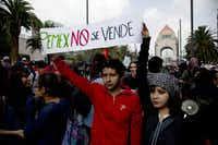 "A couple held up a banner about Mexico's state-owned oil company that says ""PEMEX is not for sale"" at a rally in Mexico City. (2013 File Photo/The Associated Press)"