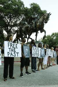 """The Dallas Peace Center and Mothers Against Police Brutality hosted a rally at Lee Park in Dallas on June 30, 2015. About 20 protesters gathered at Robert E. Lee Park in Oak Lawn to symbolically """"undedicate"""" the statue of the Confederate general, and rededicate the park to historical civil rights leaders such as Sojourner Truth and Frederick Douglass. Demonstrators also called on officials to re-evaluate Confederate symbols in the city.(Ron Baselice/Staff Photographer)"""