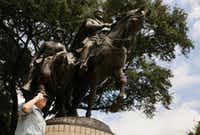 "A visitor gives the ""palm out"" Confederate salute while being photographed at Robert E. Lee Park in the Oak Lawn neighborhood of Dallas Aug. 16, 2017.(Andy Jacobsohn/Staff Photographer)"