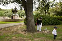 Matthew Chavez, 2, walks by as his mother Miranda Taddei (in floral headwear) gets ready for her marriage ceremony to Matthew Chavez near a statue of Confederate general Robert E. Lee at Robert E. Lee Park Aug. 16, 2017.(Andy Jacobsohn/Staff Photographer)