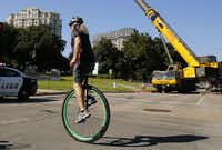 A unicyclist pedals past Lee park during attempts to remove the statue Sept. 6, 2017.(Tom Fox/Staff Photographer)