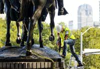 A crewman from Howell Crane and Rigging Inc. drills into the base of the statue has they had trouble removing it.(Tom Fox/Staff Photographer)