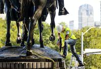 A crewman from Howell Crane and Rigging Inc. drills into the base of the statue has they had trouble removing it. (Tom Fox/Staff Photographer)
