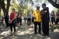 People gathered in the shade, including past local NAACP president Arthur Fleming (in yellow shirt) and pastor Clarence Glover Jr. of First African Freedom Church (right), to witness the attempted removal of the Robert E. Lee statue on Sept. 6, 2017.(Tom Fox/Staff Photographer)