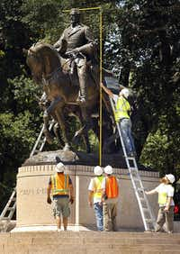 Crewmen from Howell Crane and Rigging Inc measure the height of the Robert E. Lee statue on Sept. 6, 2017.(Tom Fox/Staff Photographer)