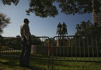 A man stops to view the statue of Confederate general Robert E. Lee in Robert E. Lee Park in Dallas Sept.  7, 2017, a day after a judge blocked the city from removing the statue after a city council vote to remove it.(Andy Jacobsohn/Staff Photographer)