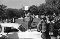 """A child holds a sign saying, """"Hi"""" while waiting for Pres. John F. Kennedy's motorcade to pass by enroute to or from the TradeMart on Nov. 22, 1963 at Lee Park, in Dallas."""