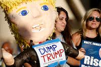 Carmen Ayala holds up a Donald Trump pinata during a support rally for DACA recipients at City Hall Plaza in Dallas on Wednesday. (Rose Baca/Staff Photographer)