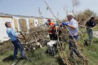 Vice President Mike Pence (center right) and Gov. Greg Abbott (in wheelchair) help move debris during a visit Rockport an area hit by Hurricane Harvey.(Eric Gay/The Associated Press)