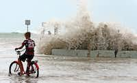 A Key West resident watches Saturday as waves crash onto a seawall in Key West, Fla.. (Charles Trainor Jr./Miami Herald)