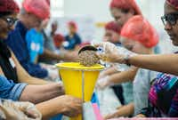 "Members of the Ismaili Muslim community and other volunteers, in partnership with Feeding Children Everywhere, pack 100,000 healthy meals Sunday at Ismaili Jamatkhana and Center in Carrollton. The meals will be d<span style=""background-color: transparent; font-size: 0.6875rem;"">elivered to victims of Hurricane Harvey.</span>(Ashley Landis/Staff Photographer)"