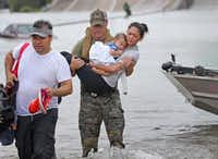 Troy Pham (left) carries their belongings as Houston SWAT Officer Daryl Hudeck carries Catherine Pham and sleeping son son Aidan to safety after they were rescued by boat from the flooding on Interstate 610 south in Houston on Aug. 27, 2017. (Louis DeLuca/Staff Photographer)