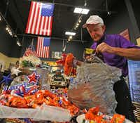 "Jim ""Mattress Mack"" McIngvale, locally famous for philanthropy and his commercials for his business, Gallery Furniture, puts out candy for customers on counters and displays at the store in north Houston on Sept. 11. (Louis DeLuca/Staff Photographer)"