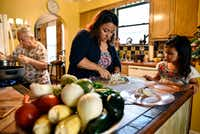 Chef Anastacia Quinones, 37, dices onion with her daughter Isabella Quinones, 4, as her mother, Maria Elena Quinones, 73, cooks ingredients.(Ben Torres/Special Contributor)