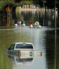Customs and Border Patrol boats look through a neighborhood which was flooded when the Barker Reservoir reached capacity in the aftermath of Hurricane Harvey Saturday, Sept. 2, 2017, in Katy, Texas. Residents gathered at the checkpoint to vent their frustrations about not being able to get back into their homes which will remain flooded for several more days while the reservoir drains. (Charlie Riedel/AP)