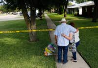 Hal Moss and daughter Kelsey Moss, of Plano, who knew three of the victims, place flowers and say a prayer for the victims loss in a shooting at the 1700 block of West Spring Creek Parkway in Plano on Tuesday, September 12, 2017. The shooting took the lives of 8 victims.(Vernon Bryant/Staff Photographer)