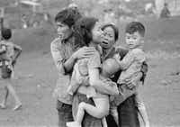 Civilians huddle after an attack by South Vietnamese forces in Dong Xoai, June 1965.(<i>The Vietnam War</i>/AP/Horst Faas)