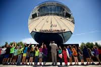 Butler Elementary fifth graders and AT&T Stadium Art Ambassador Phil Whitfield (center) wave into artist Anish Kapoor's <i>Sky Mirror</i> during an art tour at AT&T Stadium in 2016.(Brandon Wade/Special Contributor)