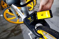 Quality control employee Sam Maskell uses the app on his smartphone to unlock a VBike smart lock box on the rear tire of a bicycle at Massimo in Garland, Texas, Thursday, September 7, 2017.(Tom Fox/Staff Photographer)