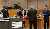 Defendant attorneys Andrew Farkas (second from right) and Maria Tu (standing to Farkas' left) sift through contents of a floral bag before it is admitted as evidence. Richardson Detective Chiron Hale (left) and prosecutor Wes Wynne look on along with District Judge Scott Becker.(Jae S. Lee/Staff Photographer)