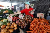 Josslyn Julka, 12, with Market Provisions places signs in each of the items offered for sale in The Shed at the Dallas Farmers Market. The signs show the buyer where each item was grown. (File Photo/Ron Baselice)